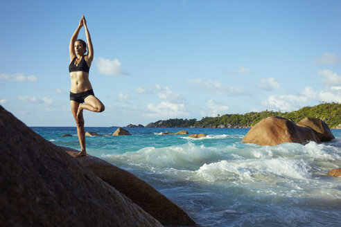 Seychelles, woman standing on a rock doing yoga exercise - ABF000605