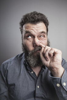 Portait of a mature man with full beard, picking his nose - MMFF000791