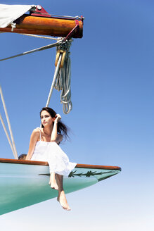 Brunette young woman on a sailing trip sitting on bow - TOYF000812