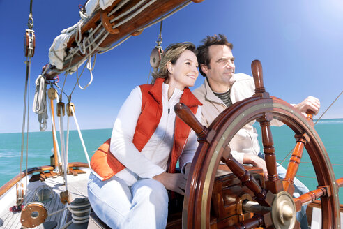 Happy mature couple at helm of a sailing ship - TOYF000819