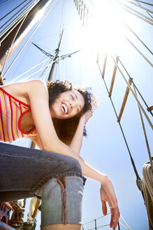 Laughing young woman on a sailing ship - TOYF000837