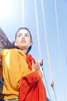Young woman holding blanket on a sailing ship - TOYF000899