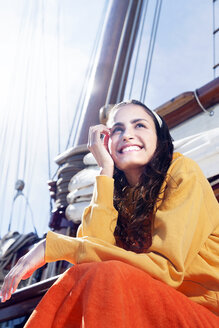 Smiling young woman on a sailing ship - TOYF000907