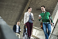 Four people walking on stairs - UUF004490