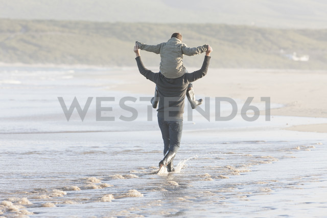 South Africa, Cape Town, man  walking on the beach carrying his son on the shoulders - ZEF005248 - zerocreatives/Westend61