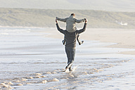South Africa, Cape Town, man  walking on the beach carrying his son on the shoulders - ZEF005248