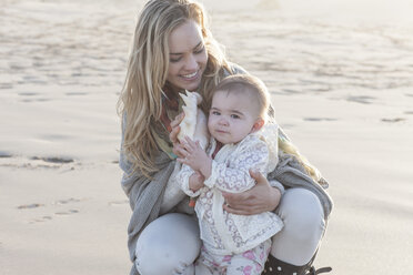 Mother and baby girl with shell on the beach - ZEF005257