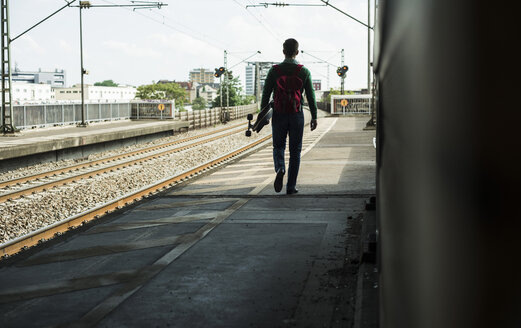 Young man with skateboard walking on railway platform - UUF004414