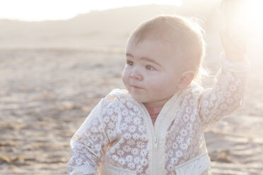 Portrait of baby girl holding mother's hand on the beach at backlight - ZEF005259