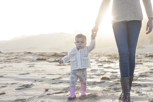 South Africa, Cape Town, baby girl holding mother's hand walking on the beach - ZEF005260