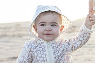 Portrait of baby girl holding mother's hand on the beach - ZEF005261