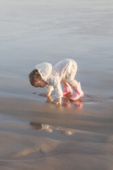 Baby girl playing at seafront on the beach - ZEF005264
