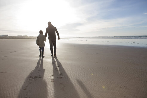 South Africa, Witsand, father and son walking on the beach at backlight - ZEF005292