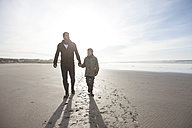 South Africa, Witsand, father and son walking on the beach at backlight - ZEF005294