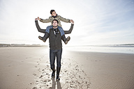 South Africa, Witsand, father carrying his son on shoulders while walking on the beach - ZEF005296