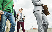 Businesspeople walking and talking outdoors - UUF004493