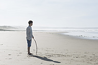 South Africa, Witsand, boy with a stick standing on the beach - ZEF005318