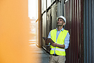 Man with digital tablet wearing reflective vest at container port - UUF004456