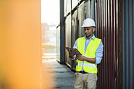 Man with digital tablet wearing reflective vest at container port - UUF004457