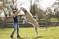 Woman training Irish Wolfhound on a meadow - TAMF000169