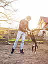 Man training his dog while Irish Wolfshound watching them - TAMF000188