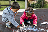 Spain, Little girl and boy drawing with chalk on the ground - MGOF000242