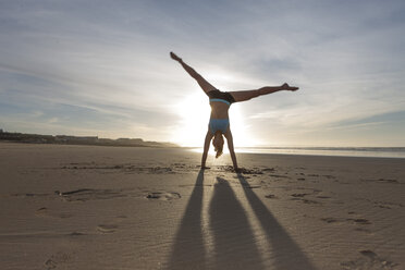 South Africa, Cape Town, silhouette of young woman doing handstand on the beach - ZEF005207