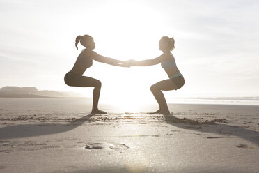 South Africa, Cape Town, two women doing stretching exercises on the beach - ZEF005211