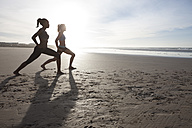 South Africa, Cape Town, two women doing stretching exercises on the beach - ZEF005434