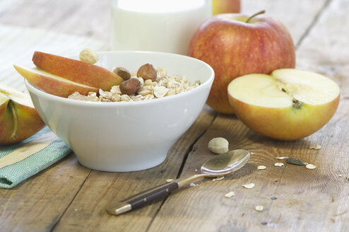 Bowl of granola and nuts with slices of an apple - ASF005616