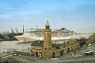 Germany, Hamburg, Clocktower at Landungsbruecken, in the background an incoming cruise ship in the morning - RJF000451