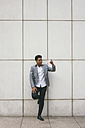 Young man leaning against a wall taking a selfie - ABZF000058
