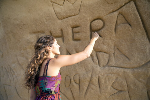 South Africa, woman carving her name on rock face - TOYF000963