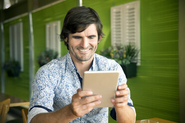 Portrait of smiling man using digital tablet in a cafe - TOYF000975