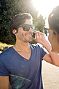 South Africa, portrait of smiling man wearing sunglasses telephoning with smartphone - TOYF000982