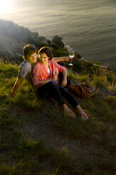 South Africa, happy couple with white wine glasses relaxing at coast in evening twilight - TOYF000988