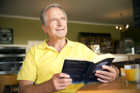 Portrait of happy senior man sitting in a cafe with a book - TOYF000998