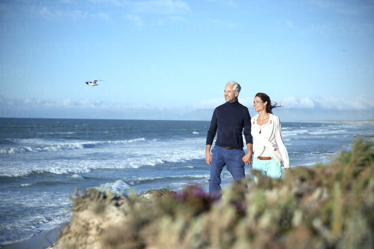 South Africa, couple walking along the coast hand in hand - TOYF001007 - Tomas Rodriguez/Westend61