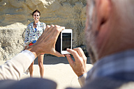 South Africa, man photographing his wife  with smartphone - TOYF001013