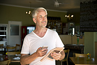 Portrait of smiling man with smartphone and newspaper - TOYF001019