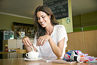 Portrait of smiling woman with cup of cappucino in a cafe - TOYF001027