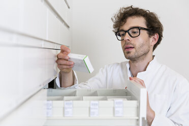 Pharmacist taking drug from a drawer cabinet - FKF001065