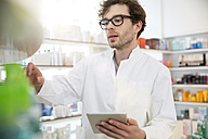 Portrait of pharmacist doing inventory control with digital tablet - FKF001068