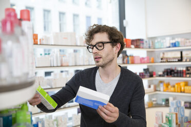 Man comparing products in a pharmacy - FKF001074