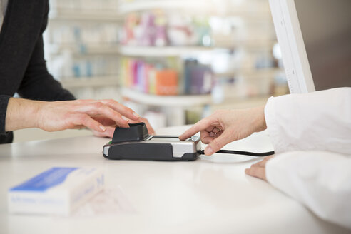 Customer paying cashless in a pharmacy - FKF001092