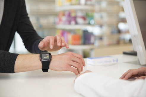 Customer showing female pharmacist his smartwatch - FKF001095