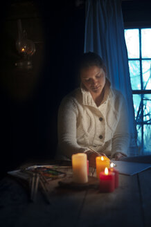 Woman painting in the evening, candle light - HHF005346