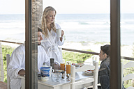 Family on patio of beach house eating breakfast - ZEF005351