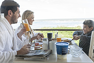 Family on patio of beach house eating breakfast - ZEF005353