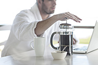 Close-up of man with coffee plunger using laptop - ZEF005358